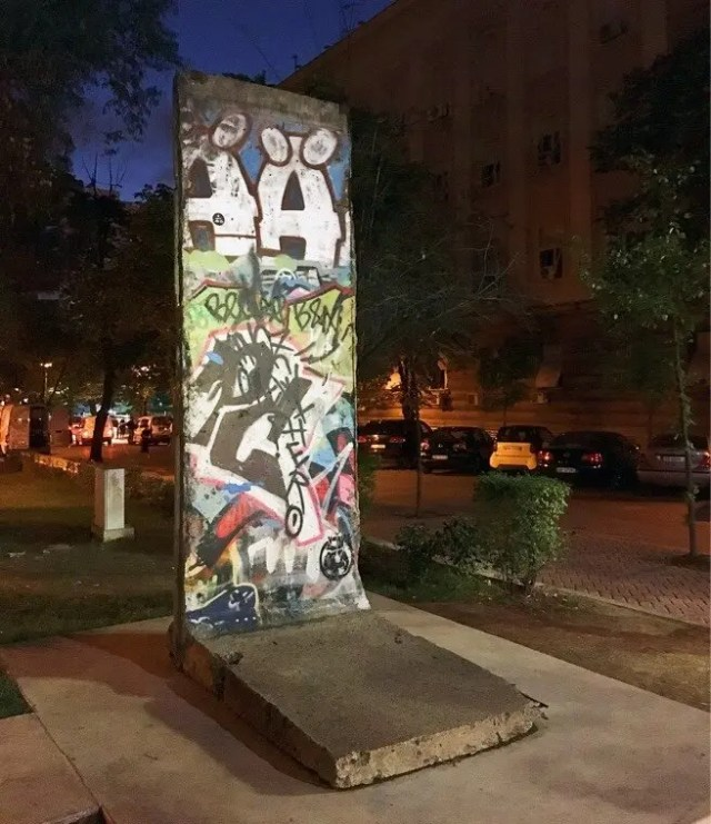 The 2.6-ton graffiti-covered slab fragment of the wall was donated by the city of Berlin. to commemorate the victims of the Communist regime.