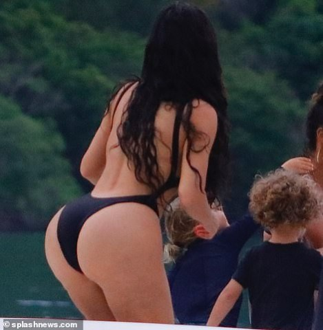 Kim Kardashian flaunts her famous backside in skimpy black swimsuit during boat day in Costa Rica