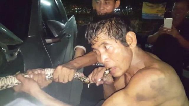 Image: Rahjit Phan biting snake trapped