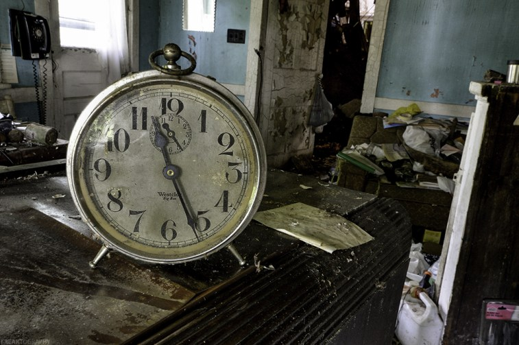 An alarm clock sits amongst filth in the kitchen of an old abandoned house.