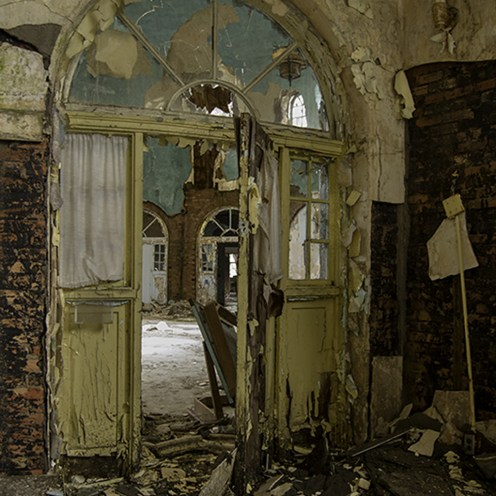 The badly decayed doorway into the stained classed capped dome in an abandoned tuberculosis hospital.