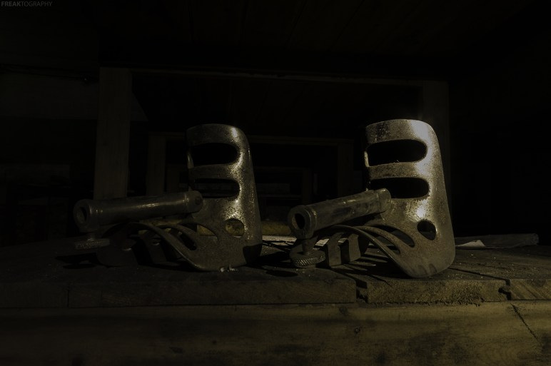 Deep in the dark basement of an abandoned mental asylum are these old steel operating table leg supports that likely date back to the early 1900's