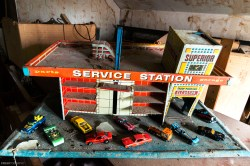 A retro tin toy service station and a collection of cast iron Hot Wheels cars that we found buried in a time capsule room upstairs in an old abandoned house.