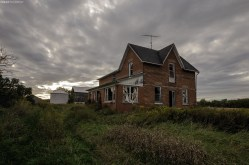 A rural Ontario abandoned farmhouse under s dark cloudy sky.