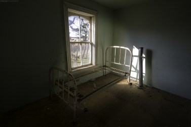 Light shining on an old bed in an abandoned ontario house.