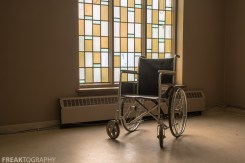 stained glass window and a wheelchair in an abandoned ontario church