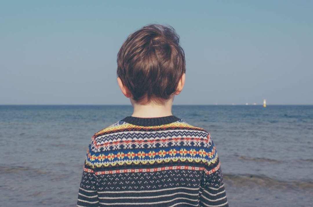 pojke tittar ut mot havet
