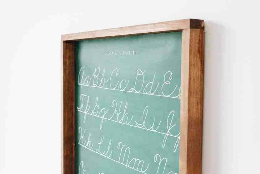 Close-up view of the Cavallini & Co Penmanship Chart with a simple wooden frame