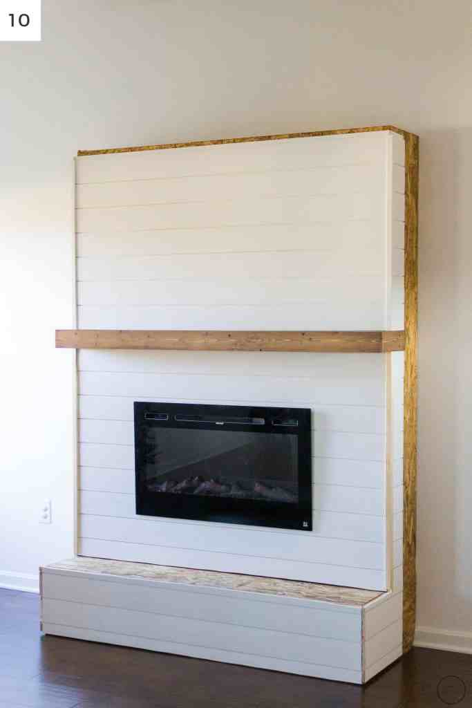 Ship lap boards being installed on a modern farmhouse electric fireplace surround and hearth