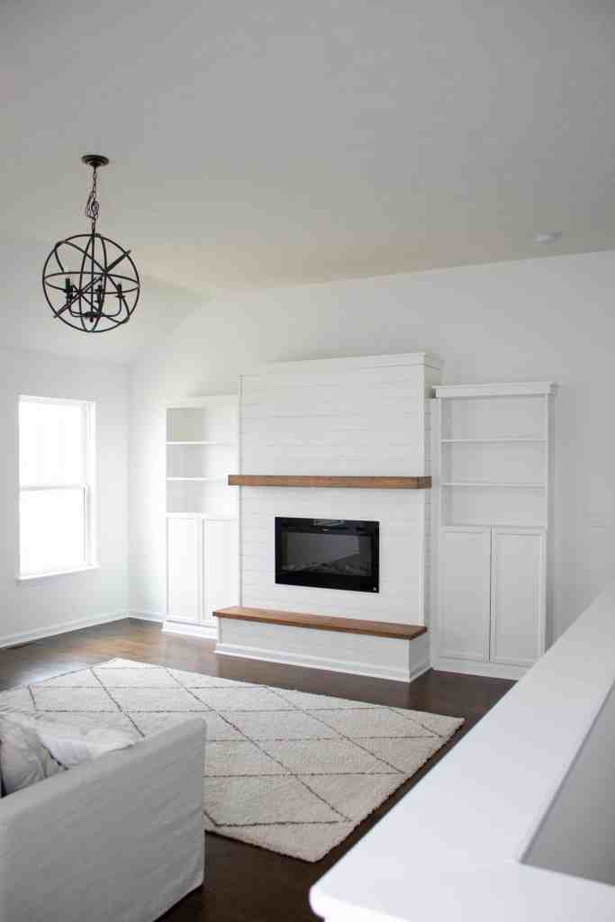 a living room featuring a custom built modern farmhouse electric fireplace feature wall with attached IKEA Billy bookcases, floating mantle, and a wooden hearth
