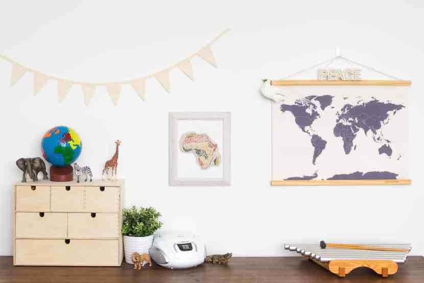 The geography corner of a Montessori-inspired homeschool room contains a continents globe, a world map, an embroidered biome map of Africa alongside several Schleich animals representative of Africa. Also included on the shelf is a CD player for children to listen to music and a pipedream instrument.