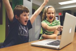 two kids excitedly look at the same laptop screen