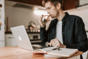 young man looking at the laptop and drinking coffee
