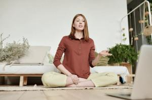 Yoga instructor in lotus position on ground interacting with laptop in front of her and leading a class