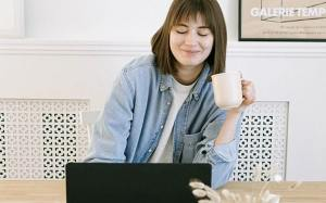 Straightforward view of smiling young woman drinking coffee while working on laptop at desk in communal working space