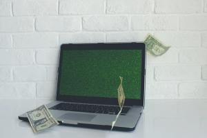 View of opened laptop against white brick wall with money floating around it