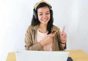 Young smiling woman seated at desk in front of laptop wearing headphones, teaching and communicating with hands against a white wall