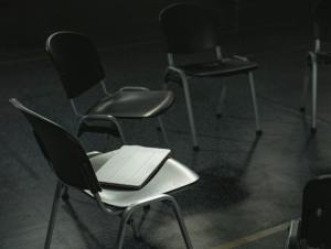 Black and white view of chairs aligned in a circle with a tablet laid down on chair in foreground.jpg