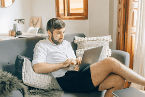 View of a casually dressed man at home working on laptop in reclined position on couch in brightly lit living room-min