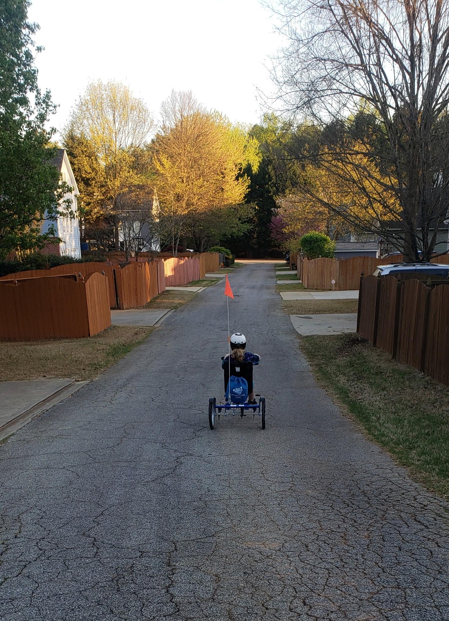 Ayden riding his adaptive bike away from the camera.