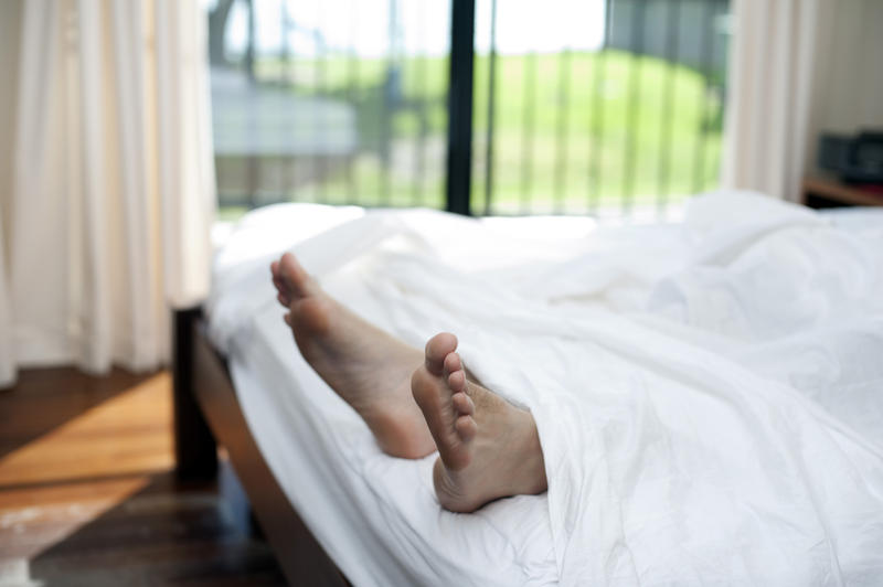 Man having a lazy day in bed with his feet protruding out from under the bedclothes with a close up view of his bare feet