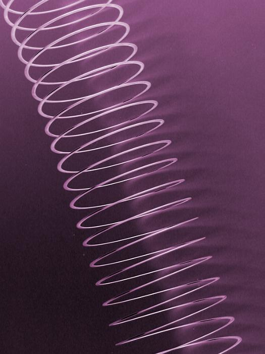 Free Stock Photo: Fully extended light weight spring toy over purple background in diagonal composition
