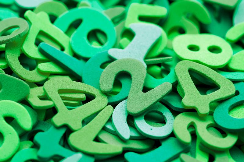 Random pile of green plastic numbers for use in a kindergarten or preschool to teach young children to count and do basic maths