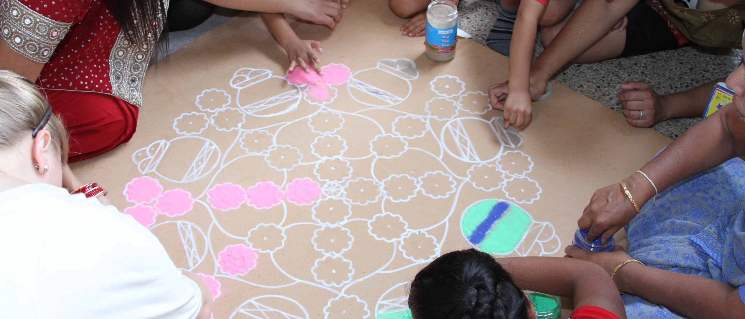 Hands drawing circles on large piece of kraft paper on the floor.