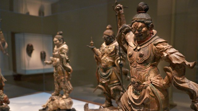 Gallery view with several small, Japanese sculptures of fearsome deities in foreground.