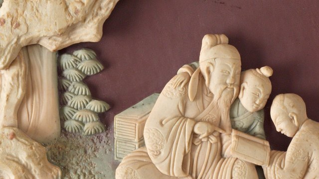 Detail of a stone plaque depicting an elderly man reading with two children.