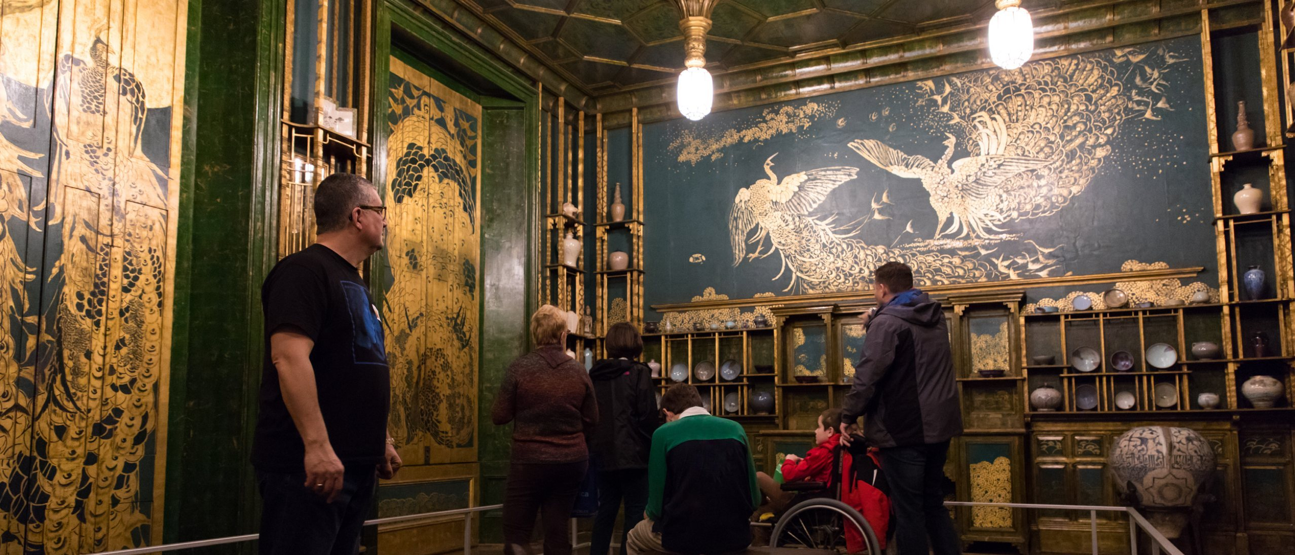 a group of visitors admiring the Peacock Room during a Morning at the Museum event