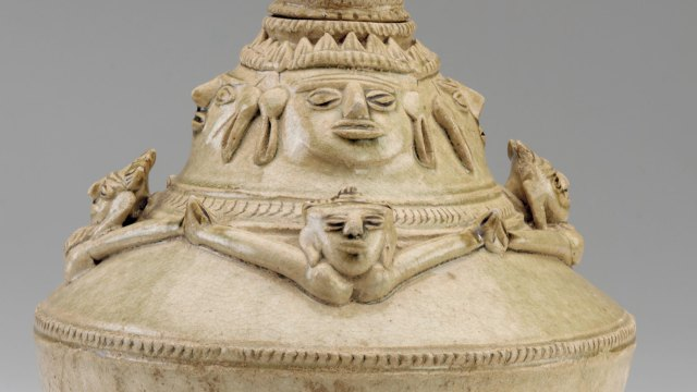 Lid detail of stoneware bottle with four male faces above four female torsos with outstretched hands