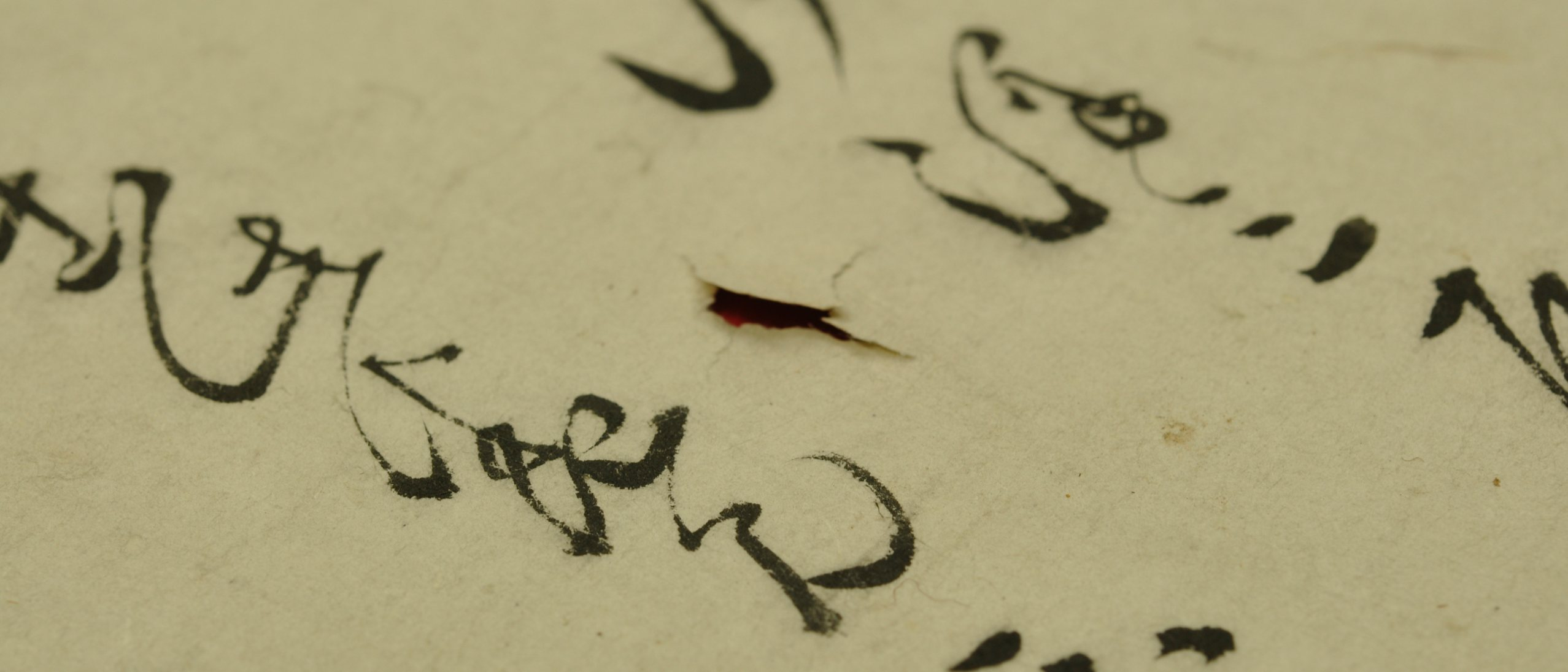 a tear in a work on paper with calligraphic script