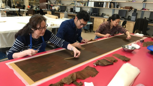three conservators working