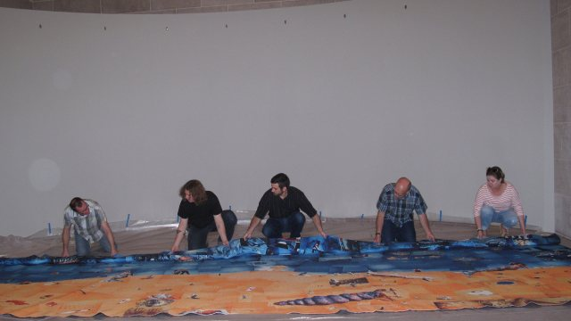 five installers working on exhibit installation