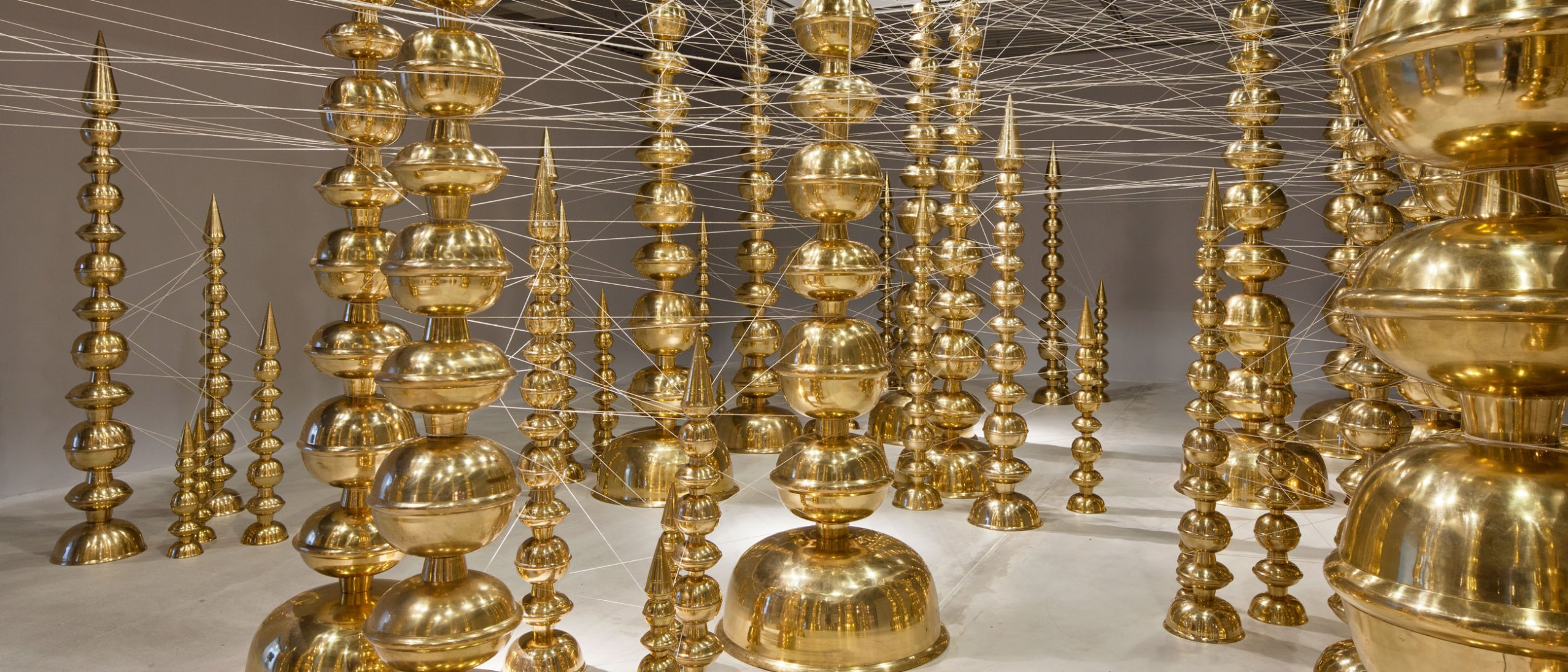 Terminal, installation: towers of brass containers connected by an intricate web of thread in the Sackler Pavilion.