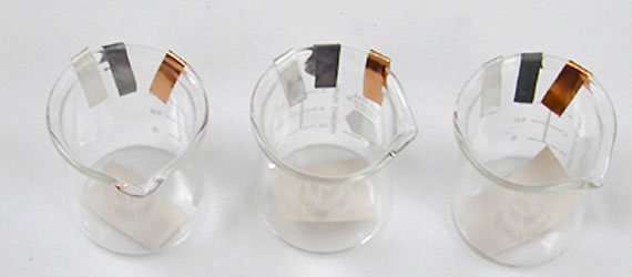 paint samples on metal strips attached to glass beakers