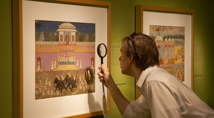 A visitor looks closely at an Indian painting in the past exhibition Garden and Cosmos