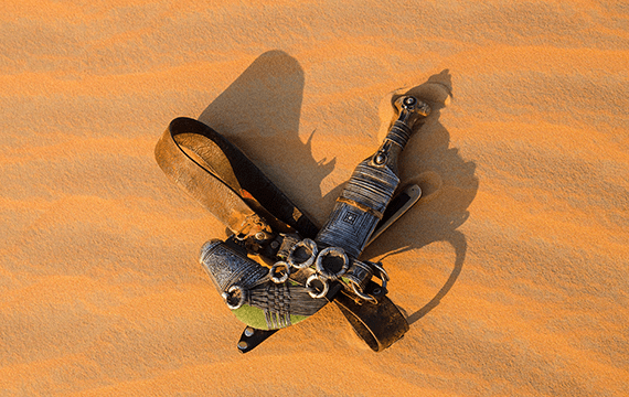A leather belt and a knife in an intricate, protective cover are laying alone on orange sand.