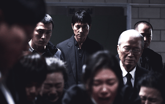 A group of Korean people dressed in black clothing. The people in the front of the group are crying (they appear the be women). The men in the back have serious expressions.