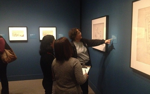 Three women are reading the caption for an art piece at the museum.