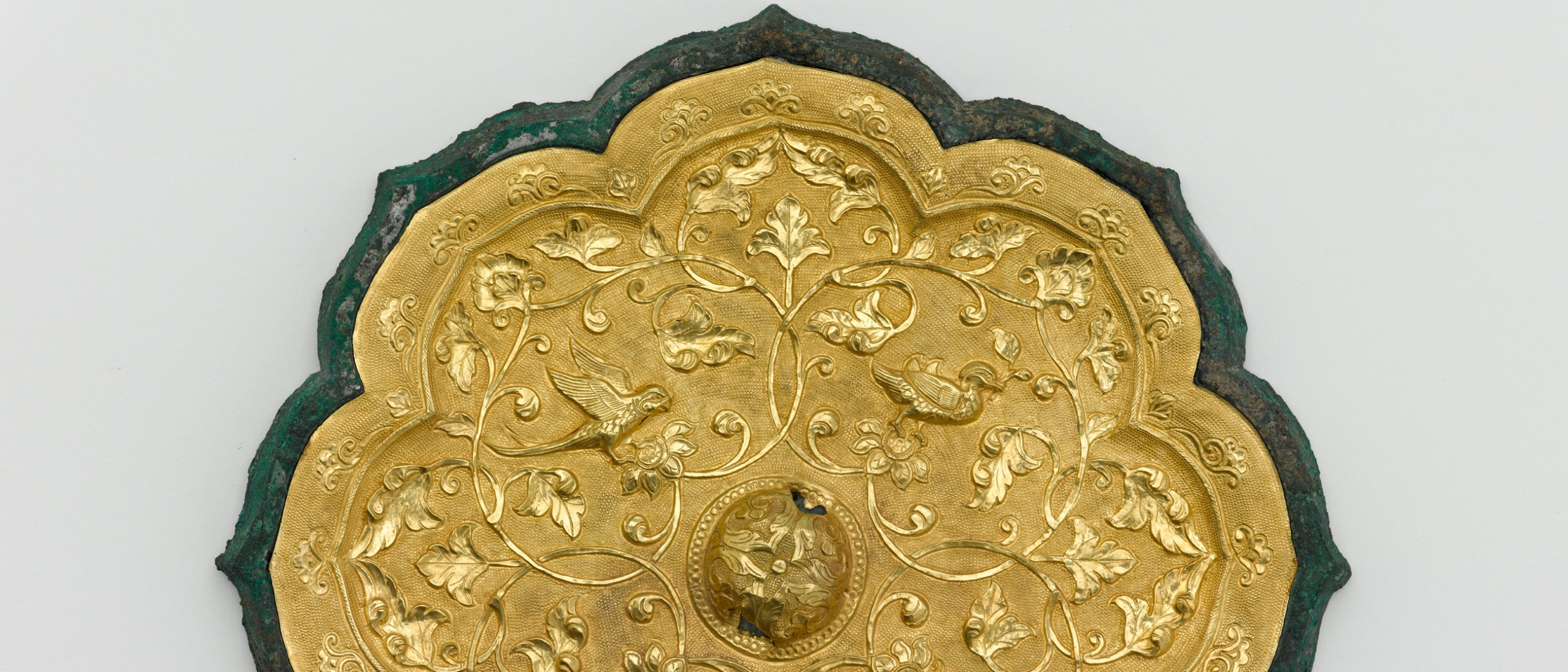 Detail image, Foliated mirror with birds and floral scrolls; Mirror; Early or mid-Tang dynasty, late 7th-early 8th century; Cast bronze and applied gold plaque with repoussé, chased, and ring-punched decoration; China; Purchase — Charles Lang Freer Endowment; Freer Gallery of Art; F1930.45
