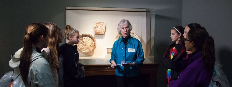 a curator discussing objects to a group of young females