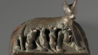 Cast bronze sculpture of a mother cat suckling four kittens.