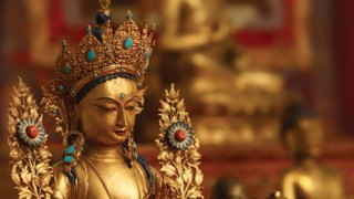 Detail of gilt copper sculpture of Tara, Tibetan Buddhist bodhisattva, with intricate turquoise and coral inlays.