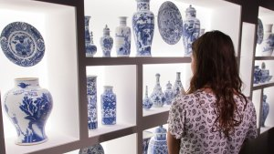 A visitor looks at blue and white china