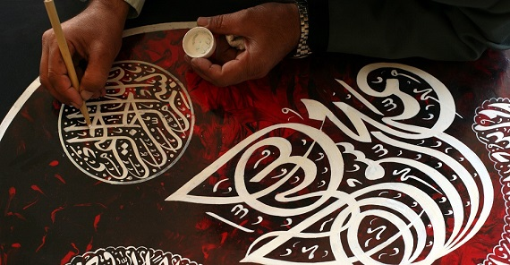 Artisan's hands paint intricate Islamic calligraphy in white ink.