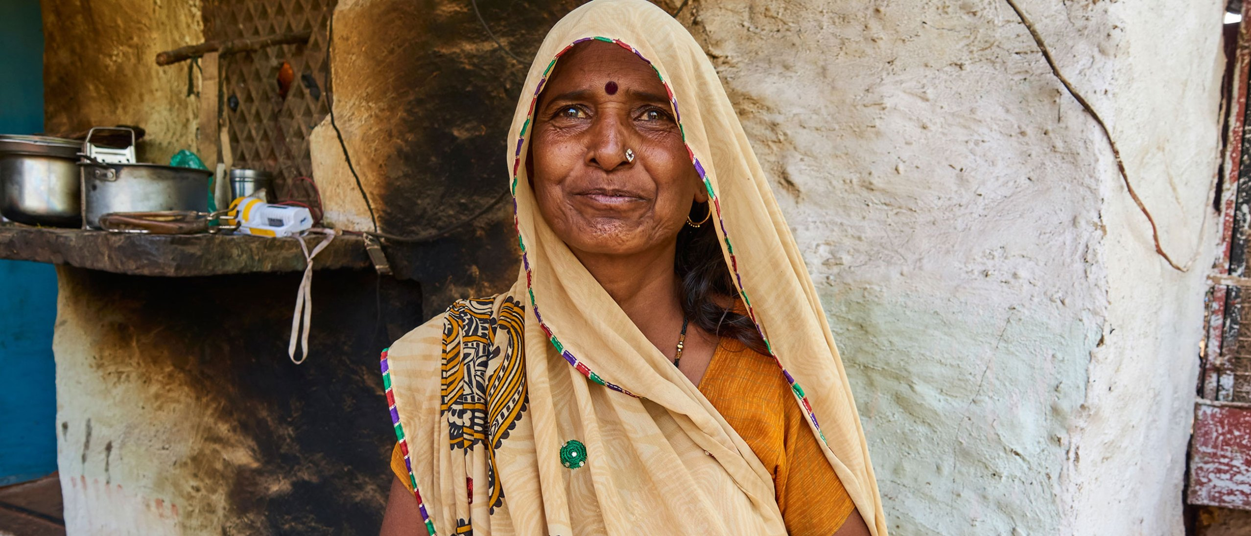 A woman in an orange sari and cream veil