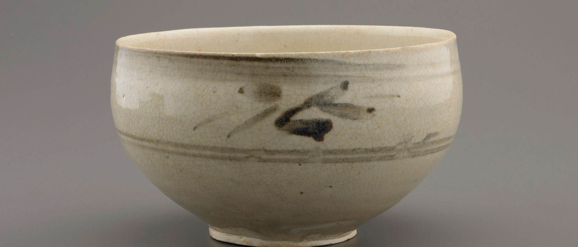 detail of a ceramic bowl, glazed a light beige, with a darker decoration