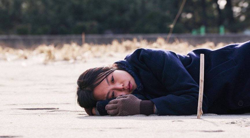 korean female in blue jacket laying on the sand